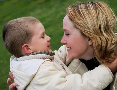 Young smiling woman is looking at little boy (focus on woman) Stock Photo - 4984280