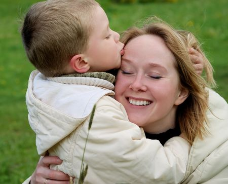 little boy kissing his mother forehead outdoor Stock Photo - 4984278