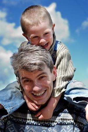 Little joyful boy sitting on the young man shoulders Stock Photo - 5027483