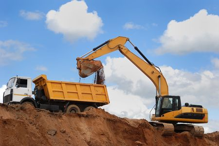 mining truck: Excavator loading sand in rear-end tipper