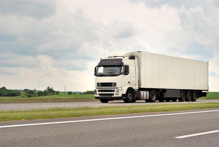 un camión de color blanco en la carretera (pasando de derecha a izquierda) Foto de archivo