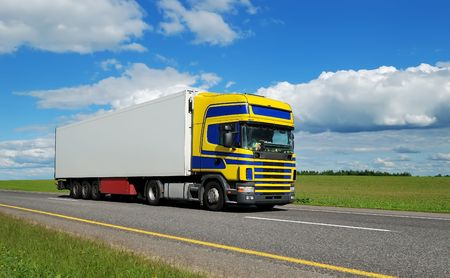 Truck (blue-yellow cabin) and white trailer moving on highway over bright sky. See my portfolio for additional beautiful vans and lorries. Stock Photo - 5364321