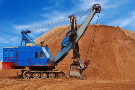 Heavy digger electric excavator standing in sandpit with huge bucket on the ground photo