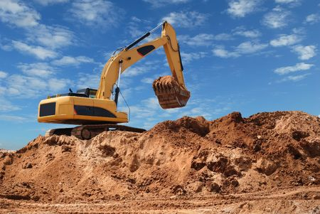 Excavator bulldozer in sandpit with raised bucket over blue cloudscape sky photo