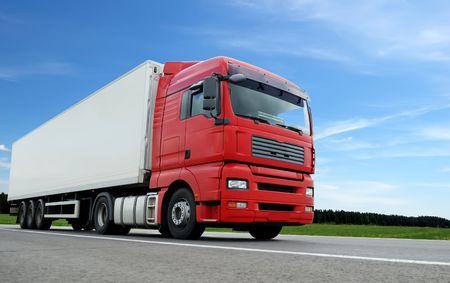 vista de la cámara baja del camión rojo con remolque blanco en la carretera más de cielo azul Foto de archivo