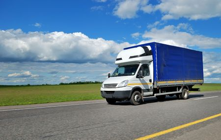 trailer: cami�n de entrega amarillo al aire libre en la carretera en azul el cielo nublado.  Foto de archivo