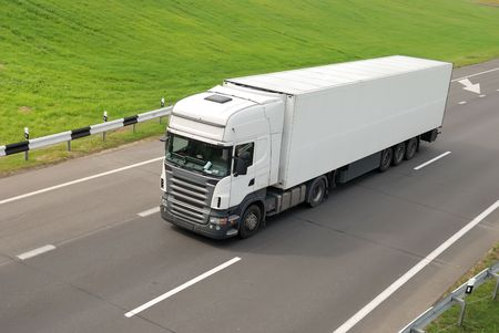 contract hauling: upper view of white lorry with trailer on the highway