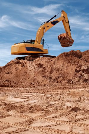 Excavator bulldozer in sandpit with raised bucket filled of sand over blue cloudscape sky photo