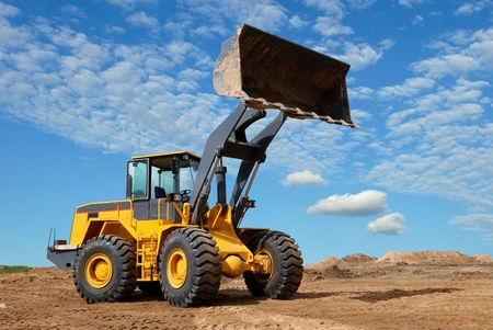 heavy equipment: wheel loader bulldozer with fully raised bucket over blue cloudy sky standing in sandpit