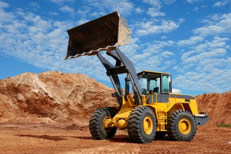 'earth mover': wheel loader bulldozer with fully raised bucket over blue cloudy sky standing in sandpit