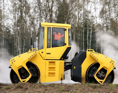 roller compactor: Heavy yellow roller compactor asphalting the road with steam