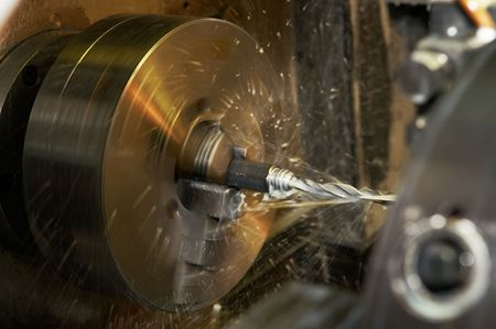 milling: Operation of drilling a hole in blank on turning machine with metal-working coolant