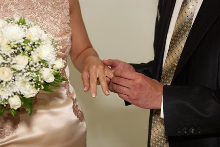 man holding womans hand and putting wedding ring on the finger photo