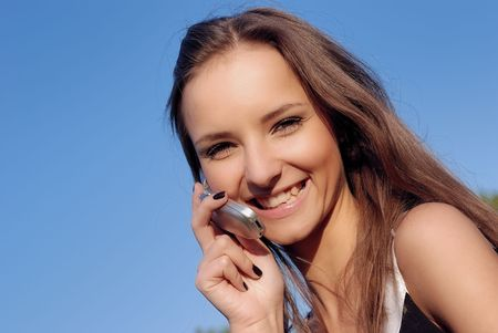 happy young woman using a mobile phone outdoors over blue sky Stock Photo - 5638305