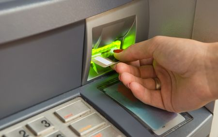 automatic teller: Cash withdrawal. Womans hand inserting plastic card Visa into the ATM Stock Photo