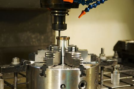 milling center: Thin mill cutting the metall blank in vertical chuck Stock Photo