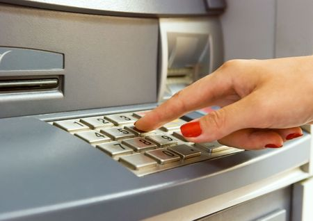 dialing: Womans hand dialing pin on bank ATM keyboard Stock Photo