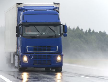 blue lorry with white trailer moving on wet road during the rain. Find more vans and trucks in my portfolio photo