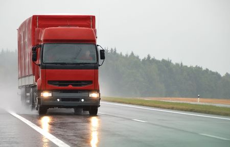 heavy rain: Red lorry with red trailer at wet road during the rain. Find more vans and trucks in my portfolio