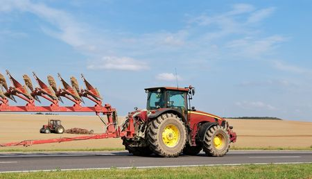 two tractors with  ploughs - one on the road, another - in field  photo