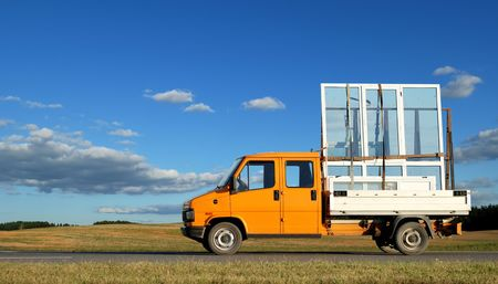 double glass: Orange minitruck transporting (delivering) winow frames and pane glasses on highway. See my other trucks and lorries