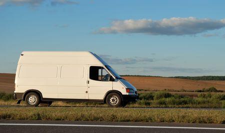 Minitruck de entrega blanco moviéndose en la carretera en el cielo azul. Ver mi cartera para camiones y camiones