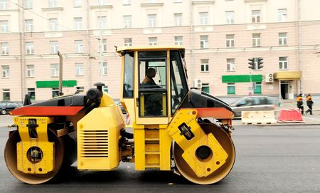 asphalting: Heavy yellow roller compactor asphalting the town road