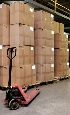 work material: Group of carton boxes and manual fork pallet truck in warehouse