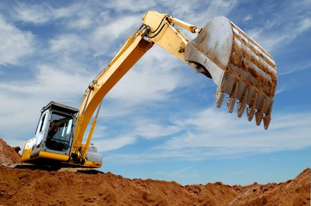 digging: Excavator standing in sandpit with raised bucket over cloudscape sky Stock Photo