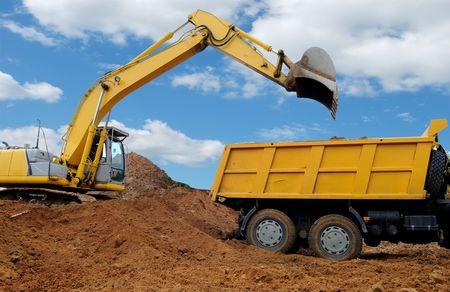 basurero: Excavadora cargando dumper cami�n volquete en fosa de arena en el cielo azul