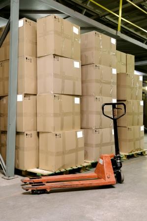 carton: Groep van kartonnen dozen en handmatige vork pallet truck in magazijn Stockfoto