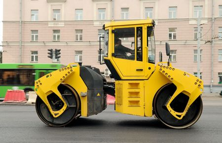 Heavy yellow roller compactor asphalting the town road photo