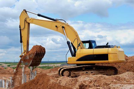 oruga: Cargador de excavadora en el sitio de construcción con arena en cubo en el cielo cloudscape