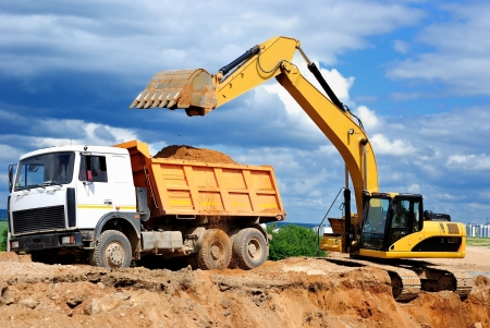 dumper: Excavator loading dumper truck tipper in sand pit over blue sky