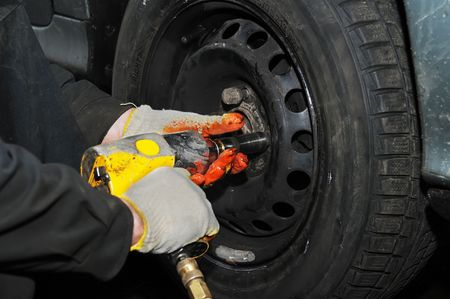 pneumatic tyres: two hands making tyre fitting with air compressed wrench (screwing up bolts) Stock Photo