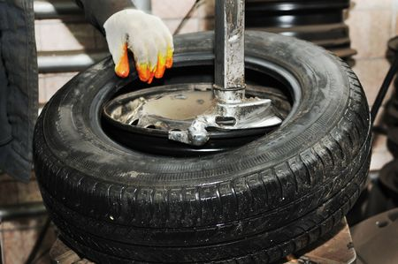 tire fitting: taking off tyre from car wheel disc for repair (replacement)