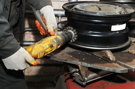 tire fitting: cleaning a car wheel disc by mechanical brush