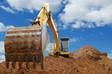 cloudscape: Excavator Loader standing in sandpit with pulled down bucket over cloudscape sky