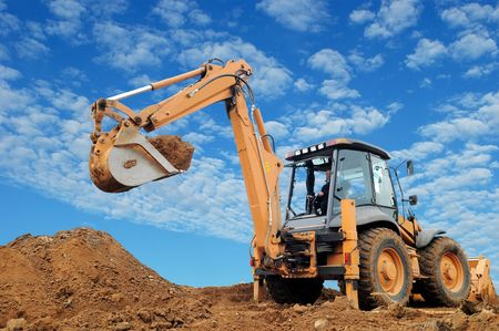 dug: Excavator Loader with rised backhoe standing in sandpit with over cloudscape sky
