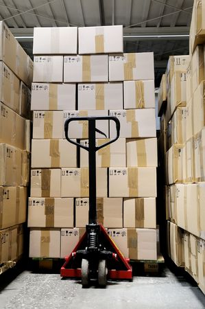 moving crate: fork pallet truck stacker in warehouse in front of cardboard boxes