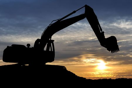 mijnbouw: silhouet van graaf machine loader op de bouw plaats met verhoogde emmer over zons ondergang