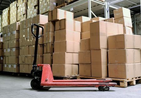 Group of carton boxes and fork pallet truck stacker in warehouse in front of cardboard boxes photo