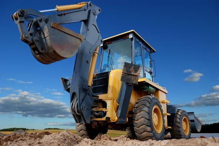 digging: Excavator Loader with raised backhoe standing over cloudscape sky Stock Photo