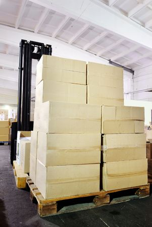 Electric forklift stacker in warehouse behind the cardboard boxes photo