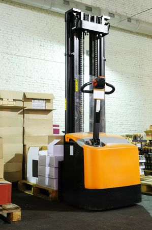 moving crate: rear view of an electric forklift stacker in warehouse with the cardboard boxes on the pallet