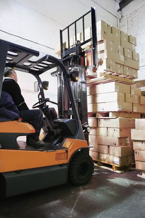 safety box: Electric forklift in warehouse loading cardboard boxes