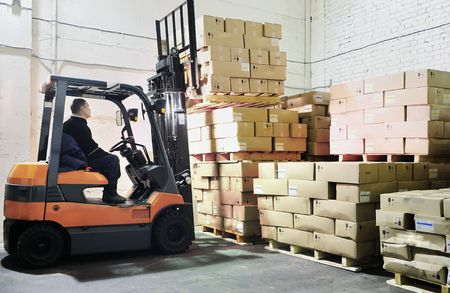 moving crate: Electric forklift in warehouse loading cardboard boxes