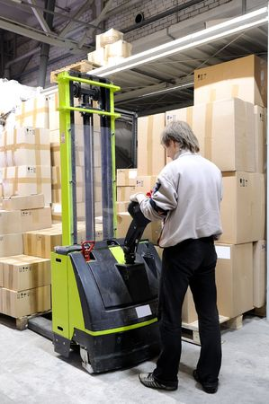 Man with electric forklift stacker truck in warehouse loading Group of cardboard boxes photo