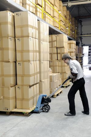 moving crate: Man with fork pallet truck stacker in warehouse loading Group of cardboard boxes