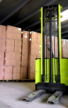 Electric forklift stacker in warehouse in front of cardboard boxes photo